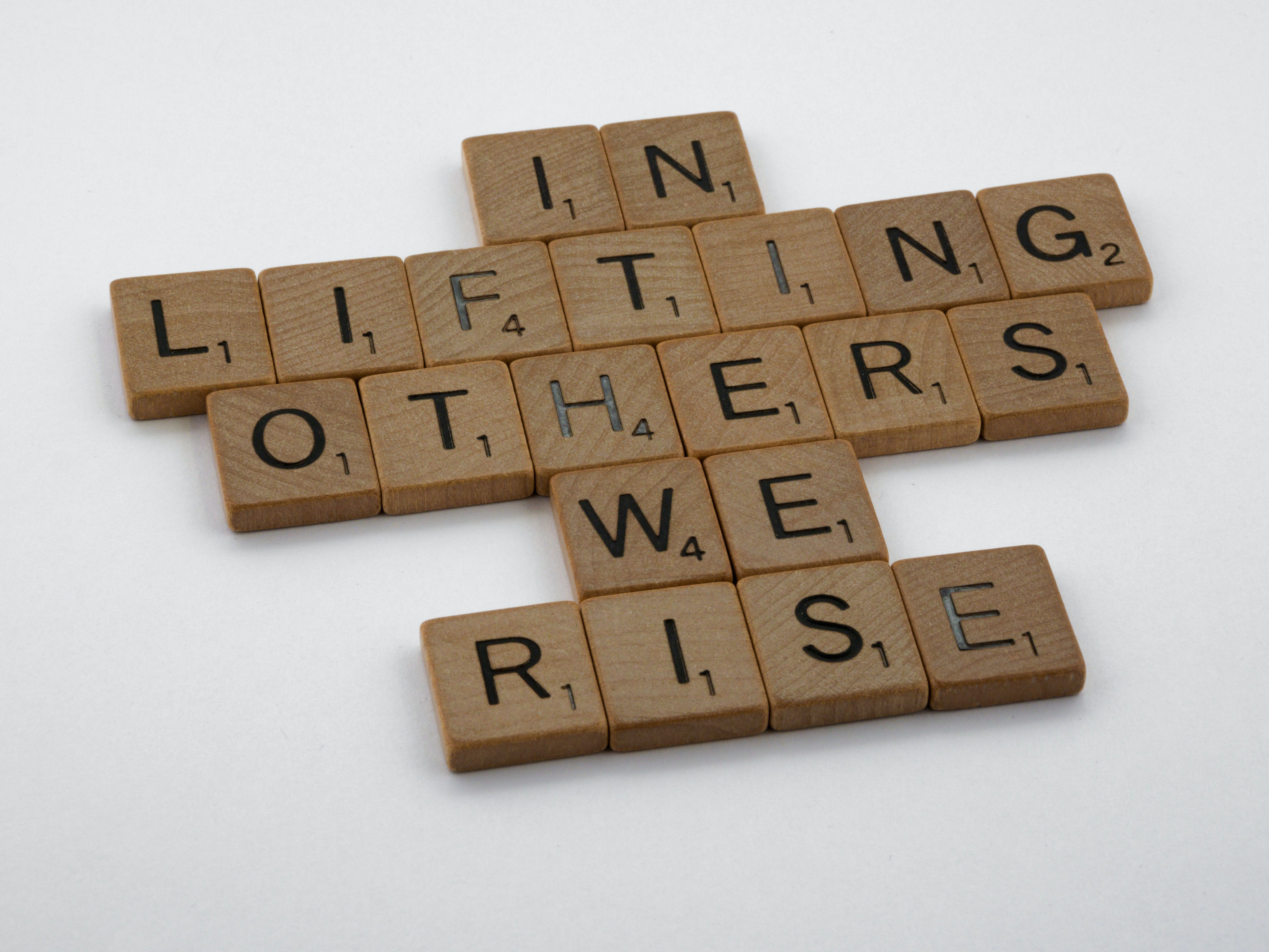 Scrabble chips that say in lifting others we rise