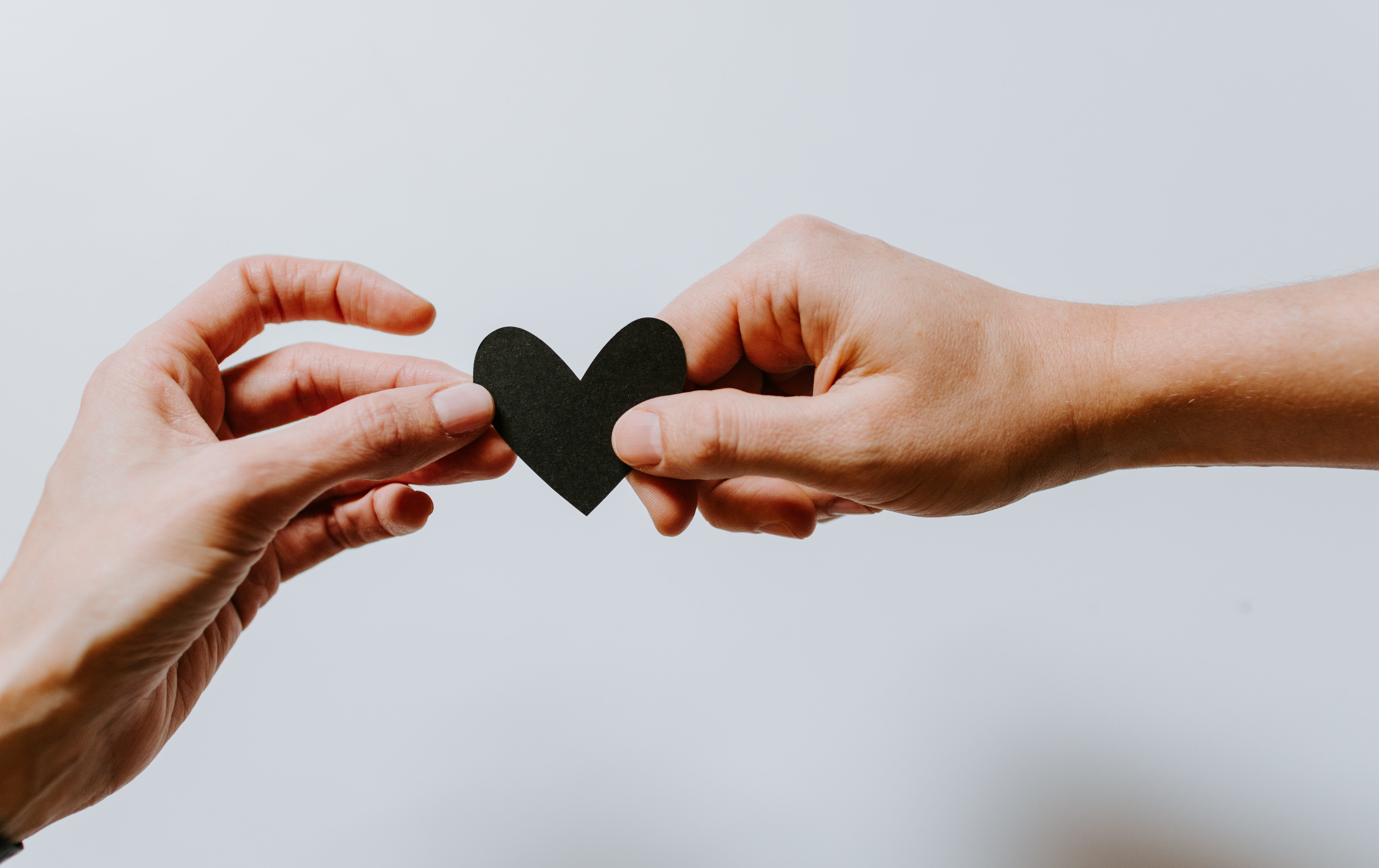 Hands holding two sides of a heart
